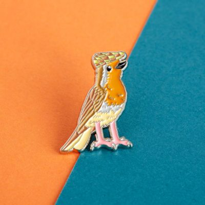Robin in a flat cap enamel pin by Alice Tams