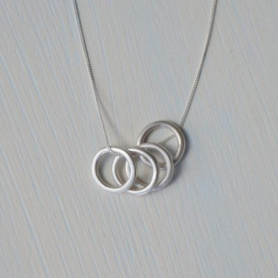 "Minimalistic circles necklace made up of 4 Sterling Silver small rings on a chain. The simplistic style makes it an everyday favourite; perfect for layering or for wearing on its own. A satin (light 'matt') finish is applied to give a soft sheen to the metal which gives a shimmering shine and a contemporary look and feel. Please be aware it is not a super-shiny finish; my photos give an accurate view of how the finished item will look. Each ring measures approximately 1.4cm diameter. The chain measures 18"" / 45cm in length which I think works best, however, if you would like a different chain length then please send me a message at the checkout. All of my jewellery will arrive in a Darte branded gift box which is made from 100% eco-friendly cardboard. Each jewellery box has a matt kraft paper finish with a natural look and comes with a soft black foam insert and silver metallic foil logo. Perfect for giving jewellery as a gift or for storing your jewellery in. All jewellery is handmade by me. Although I try to keep consistency across each product, please note your piece may vary very slightly to the picture shown."