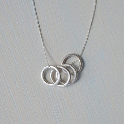 """Minimalistic circles necklace made up of 4 Sterling Silver small rings on a chain. The simplistic style makes it an everyday favourite; perfect for layering or for wearing on its own. A satin (light 'matt') finish is applied to give a soft sheen to the metal which gives a shimmering shine and a contemporary look and feel. Please be aware it is not a super-shiny finish; my photos give an accurate view of how the finished item will look. Each ring measures approximately 1.4cm diameter. The chain measures 18"""" / 45cm in length which I think works best, however, if you would like a different chain length then please send me a message at the checkout. All of my jewellery will arrive in a Darte branded gift box which is made from 100% eco-friendly cardboard. Each jewellery box has a matt kraft paper finish with a natural look and comes with a soft black foam insert and silver metallic foil logo. Perfect for giving jewellery as a gift or for storing your jewellery in. All jewellery is handmade by me. Although I try to keep consistency across each product, please note your piece may vary very slightly to the picture shown."""